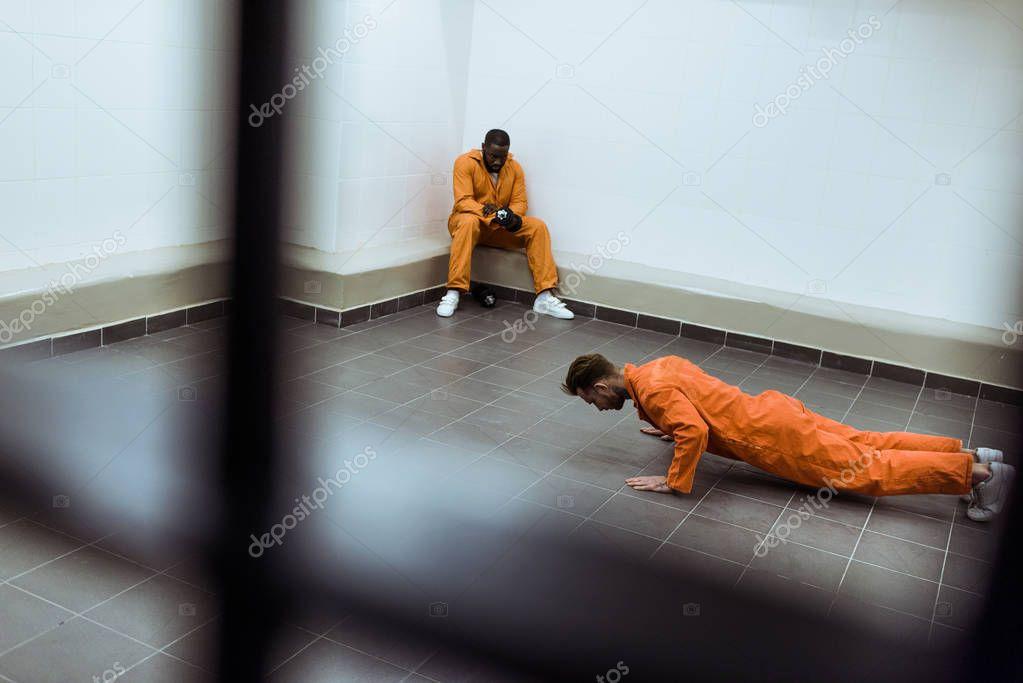 prisoner doing push-ups on floor in prison cell