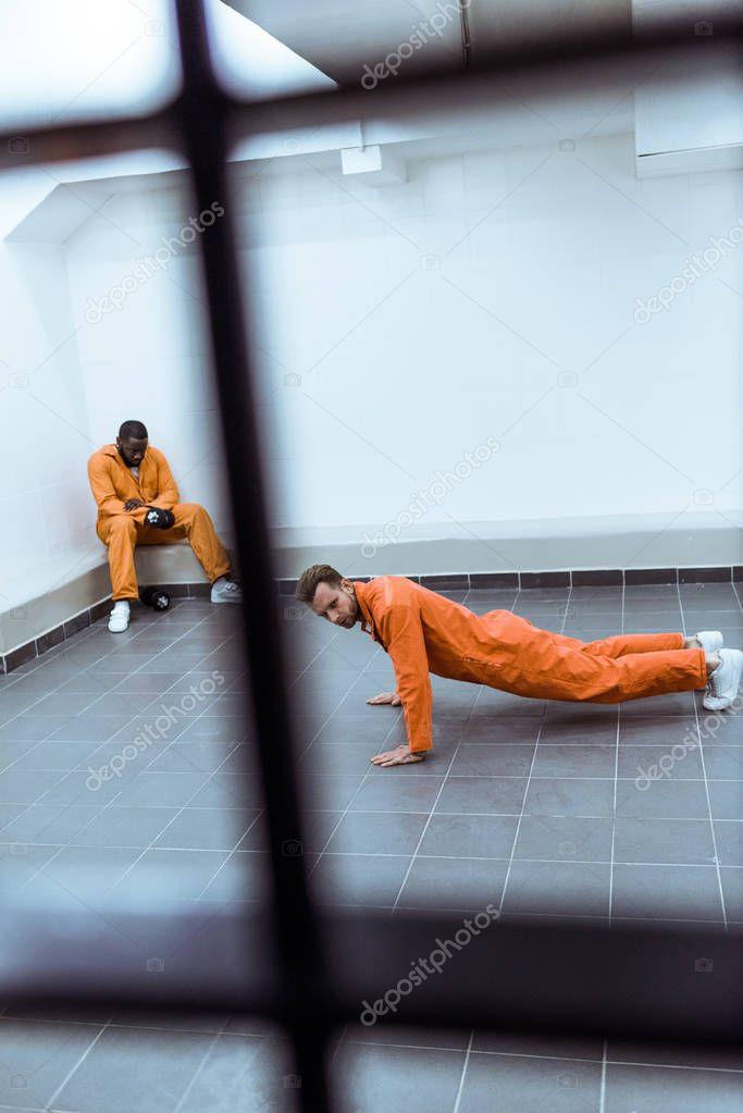 prisoner doing push-ups in prison cell