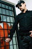 Africký Americký zajatec dávat peníze do vězeňské stráže jako úplatek