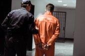 zadní pohled na vězení důstojník předních vězně v poutech v chodbě