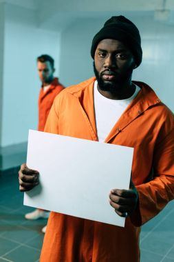 african american prisoner holding blank placard and looking at camera