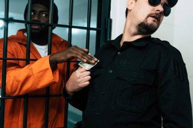 african american prisoner giving money to prison warden as bribe