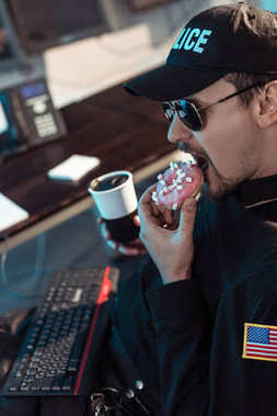 prison guard eating doughnut and holding cup of coffee