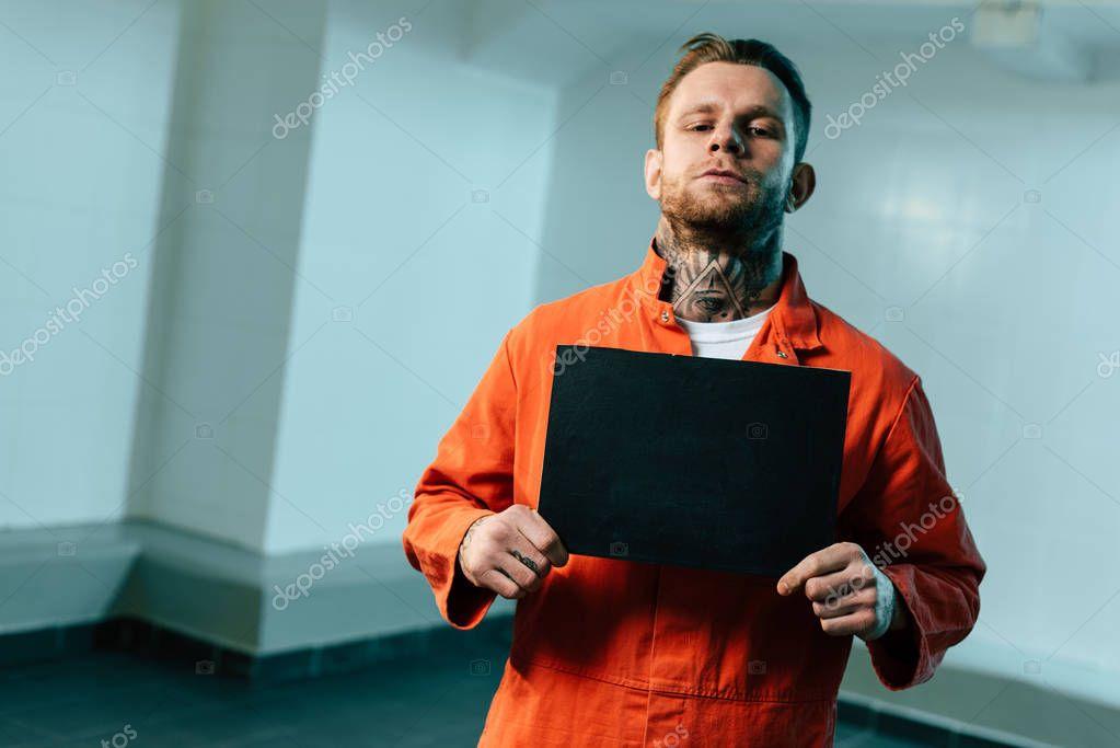 prisoner holding blackboard and looking at camera