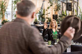 Fotografie selective focus of woman waving to man while sitting at table in cafe