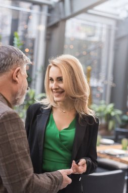 partial view of smiling woman and man looking at each other in cafe