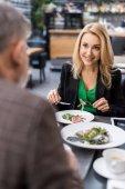 částečný pohled na člověka a usmívající se žena společná večeře v restauraci