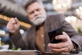 Fotografie Selektivní fokus podnikatele pomocí smartphone v kavárně