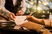 Schnappschuss einer Geschäftsfrau bei Vertragsunterzeichnung während eines Treffens mit einem Geschäftspartner im Café