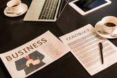 zblízka pohled uspořádány digitálních zařízení, obchodní noviny, šálky kávy a smlouvu na desku stolu