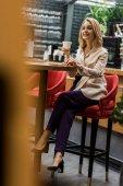 Selektivní fokus usmívající se žena s šálkem kávy v kavárně