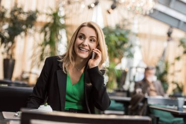 portrait of smiling businesswoman talking on smartphone in cafe