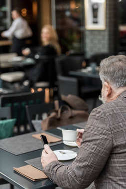 back view of senior businessman with smartphone and cup of coffee in cafe