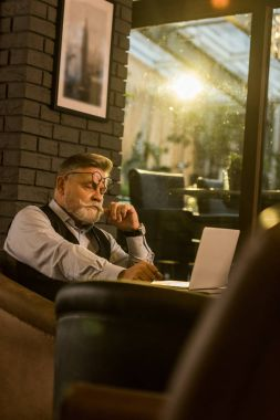 side view of pensive senior businessman sitting at table with laptop in cafe