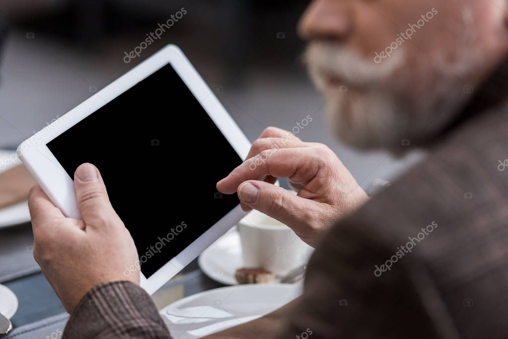 partial view of businessman with tablet with blank screen in cafe