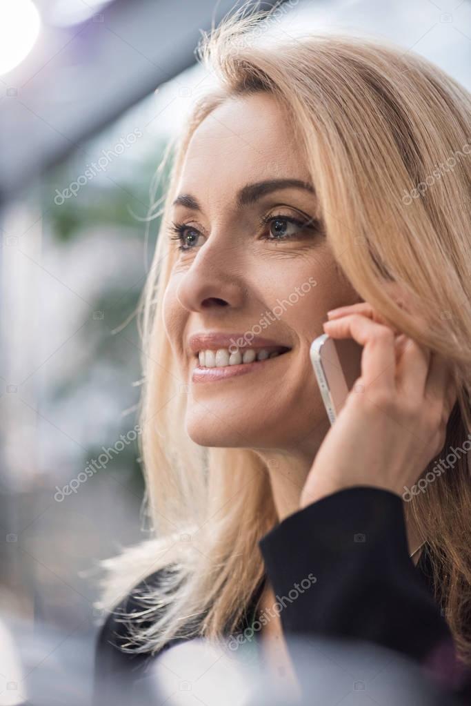 portrait of smiling businesswoman talking on smartphone