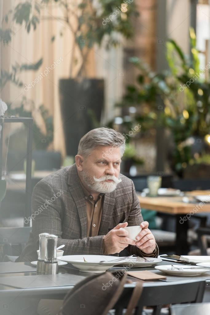 portrait of senior man with cup of coffee in cafe
