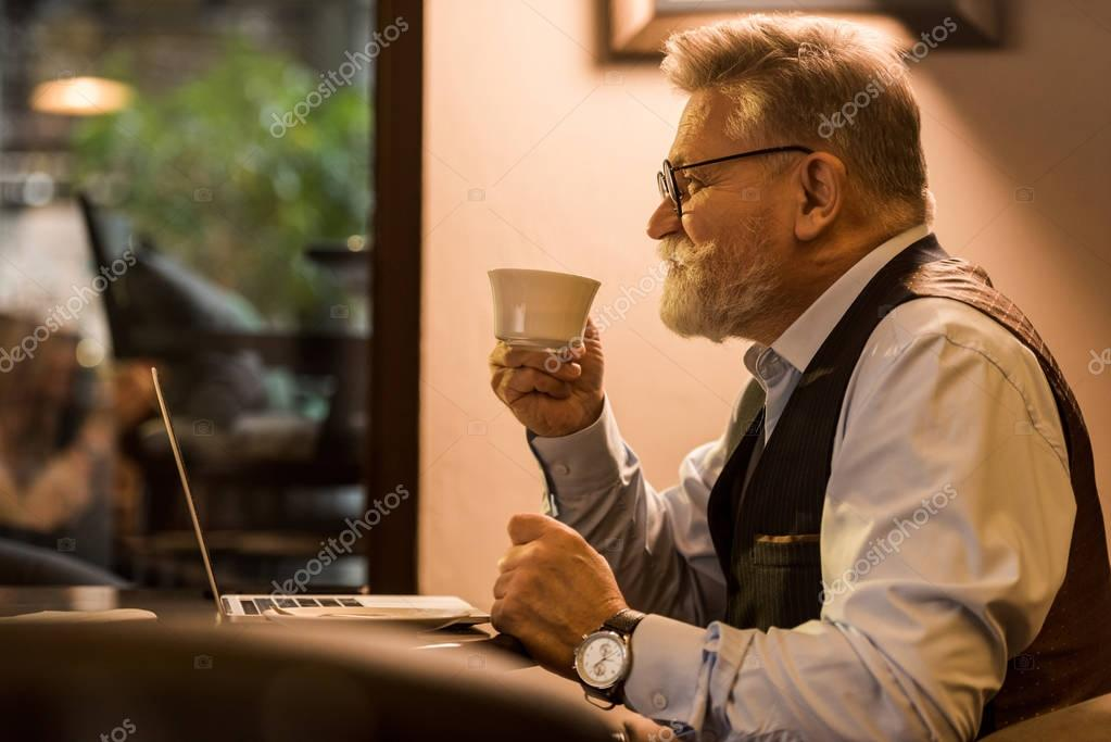 side view of senior bearded businessman with cup of coffee sitting at table with laptop in cafe