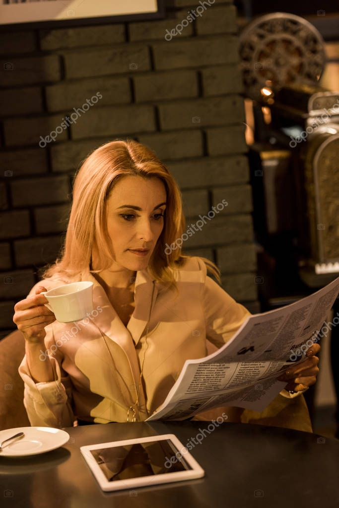 portrait of businesswoman with cup of coffee reading newspaper in cafe