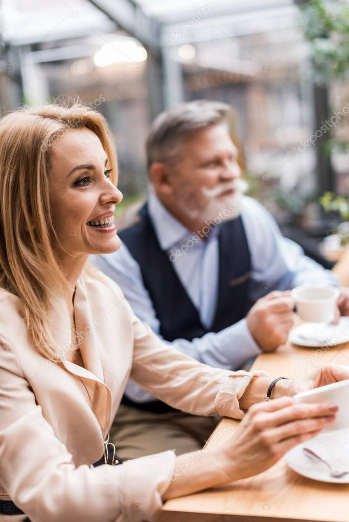 selective focus of couple drinking coffee on romantic date in cafe
