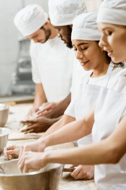 group of multiethnic bakers kneading dough together