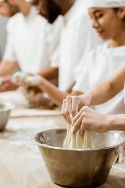 cropped shot of group of baking manufacture workers kneading dough