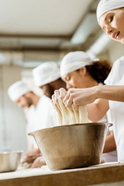 close-up shot of group of baking manufacture workers kneading dough together
