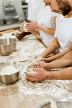 cropped shot of group of baking manufacture workers kneading dough together