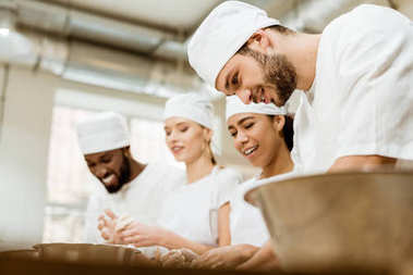 group of happy baking manufacture workers kneading dough together