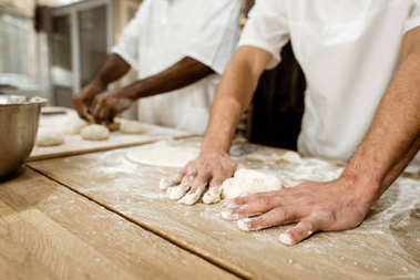 cropped shot of bakers kneading dough together at baking manufacture