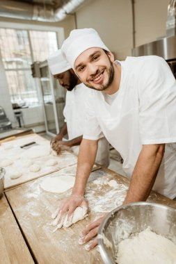 happy handsome bakers kneading dough together at baking manufacture
