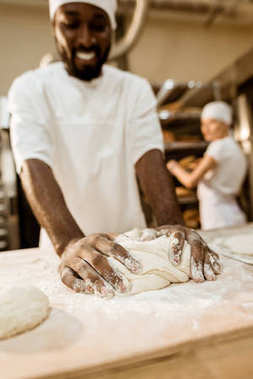 close-up shot of african american baker kneading dough at baking manufacture