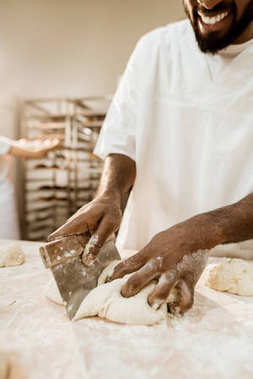 cropped shot of african american baker cutting dough with dough knife