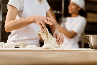cropped shot of female baker kneading dough at baking manufacture