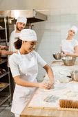 Fotografie multiethnische Team der Bäcker backen Herstellung zusammenarbeiten