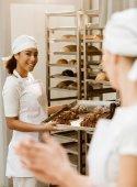 Fotografie junge weibliche Bäcker backen gemeinsam fertigen Abd im Gespräch