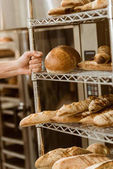 Fotografie baker holding shelves with fresh loaves of bread on baking manufacture