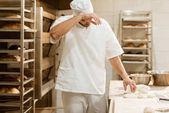 erschöpft Bäcker arbeiten mit rohen Teig zu backen Herstellung und Schweiß abwischen