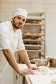 Fotografie hübscher Junge Bäcker mit rohen Teig am Arbeitsplatz auf Backen Herstellung