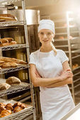 young female baker with crossed arms leaning on shelves with freshly baked bread on baking manufacture