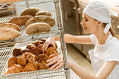 young female baker doing examination of freshly baked croissants on baking manufacture