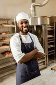 Fotografie lächelnde afrikanische amerikanische Bäcker mit verschränkten Armen auf Backen Herstellung