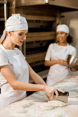 young female baker cutting dough with dough knife at baking manufacture while her colleagues working blurred on background