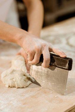 cropped shot of baker cutting dough with dough knife