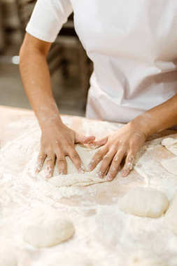 cropped shot of female baker kneading dough for pastry on messy table