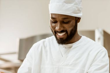 smiling handsome african american baker in hat on baking manufacture