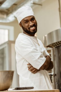 handsome african american baker with crossed hands looking at camera on baking manufacture