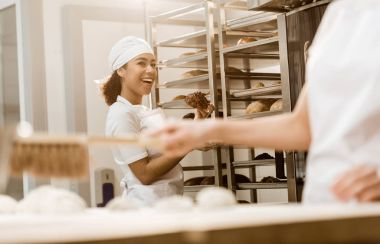 young female baker talking to colleague at baking manufacture while she cleaning workplace from flour