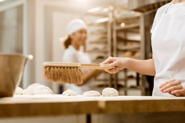 cropped shot of baker cleaning workplace from flour with brush at baking manufacture