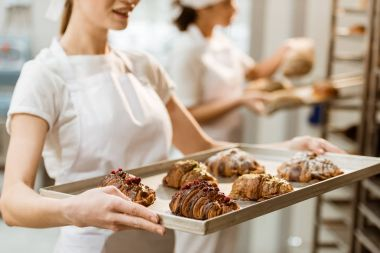 cropped shot of young baker holding tray with fresh croissants at baking manufacture